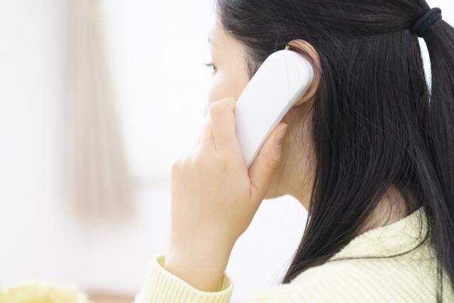 電話で水道修理を依頼する女性